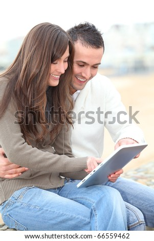 Young couple using electronic pad by the beach in winter - stock photo