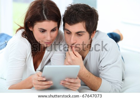 Young couple using electronic tab on sofa