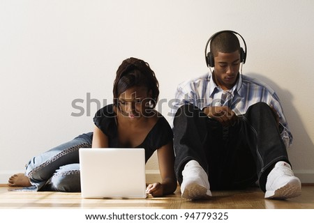 Young couple using laptop and headphones - stock photo