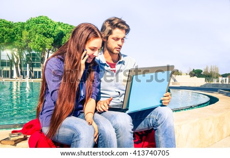 Young couple using laptop and mobile phone sitting on urban tub - Unemployed youth seeking job on line by pc internet connected - Social concept about new generations unemployment and work issue - stock photo
