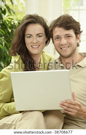 Young couple using laptop computer at home, sitting at couch, looking at camera, smiling.