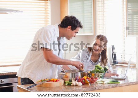Young couple using laptop to look up recipe for their meal - stock photo