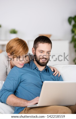 Young couple using laptop together in living room