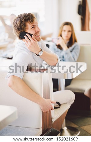 Young couple using mobile phones in a cafe. Shallow DOF, focus on man's eye. - stock photo