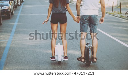 Young couple using segway on road