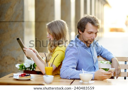 Young couple using smart phone and tablet pc in the outdoor cafe  - stock photo