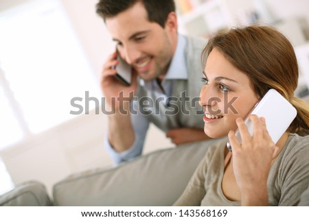 Young couple using smartphone at home - stock photo
