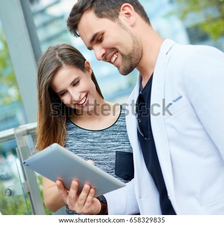 Young couple using tablet, smiling happy outdoors.