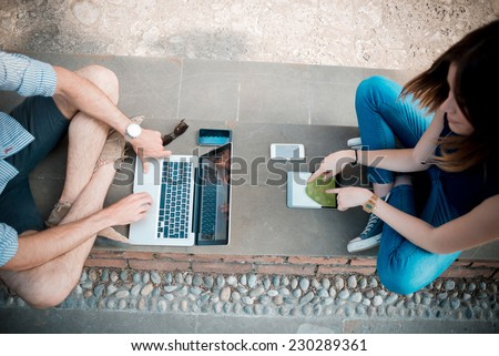 young couple using technology multitasking smartphone tablet and notebook in the street - stock photo