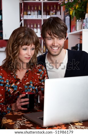 Young couple using their laptop and sitting at a table - stock photo