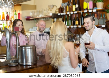 Young couple waiting for table in restaurant and drinking wine at tavern. Focus on the man - stock photo