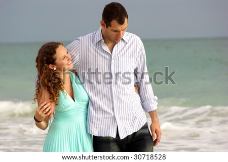 young couple walking along bonita beach in florida at the gulf of mexico having a discussion with waves crashing behind them. Woman is smiling and looking up at her man. - stock photo