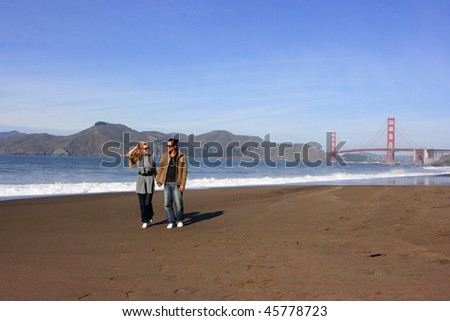 Young couple walking along the beach with Golden Gate bridge on background