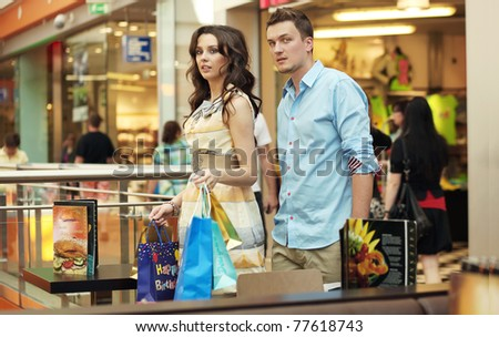 Young couple walking at shopping passage - stock photo