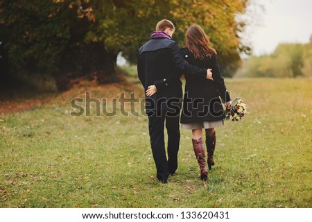 young couple walking away, autumn day - stock photo