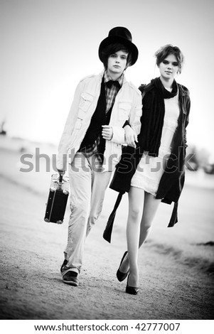 Young couple walking. Contrast black and white colors. - stock photo