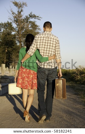 Young couple walking down path with their vintage suitcase in hand.They have arm around each other. - stock photo