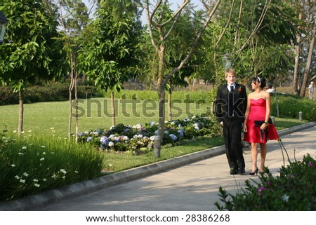 Young couple walking in a park dressed in formal wear. - stock photo