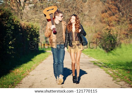 Young couple walking in a romantic mood with guitar outdoors in a park. - stock photo