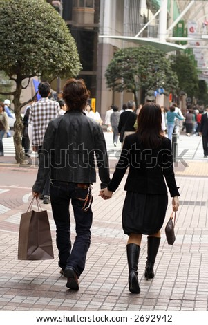 Young couple walking in a urban shopping area. - stock photo