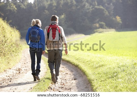 Young couple walking in park - stock photo