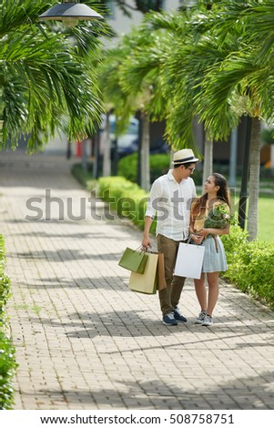 Young couple walking in park after shopping