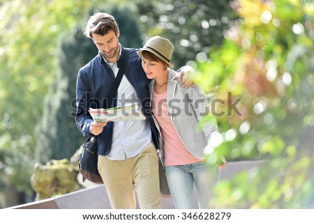 Young couple walking in park and reading city map