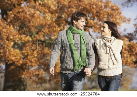 Young Couple Walking In Park Holding Hands - stock photo