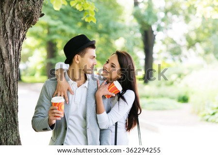 Young couple walking in the park together drinking coffee. - stock photo