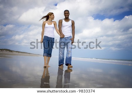 Young couple walking on a beach - stock photo