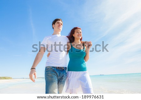 Young Couple Walking on a Caribbean Beach - stock photo