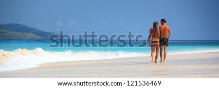 Young couple walking on a perfect tropical sandy beach - stock photo