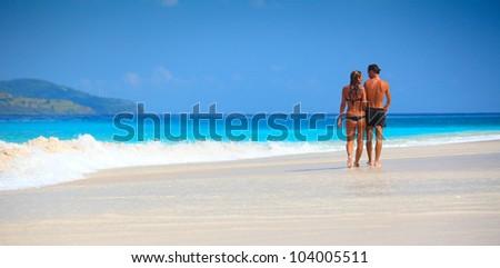 Young couple walking on a sandy beach along a coastline - stock photo