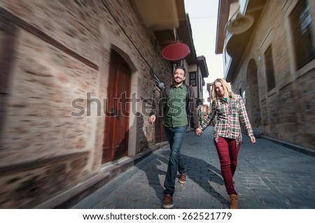 Young couple walking outdoors in old European town. Romantic happy woman and man holding hands enjoying life and romance outside. Multiracial Caucasian Arabic couple. - stock photo