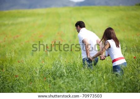 Young couple walking through green field. - stock photo