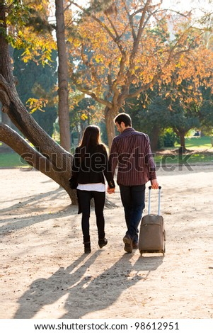 Young Couple walking together in park with traveling trolley. - stock photo