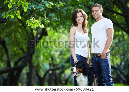 Young couple walking with a dog in the park - stock photo