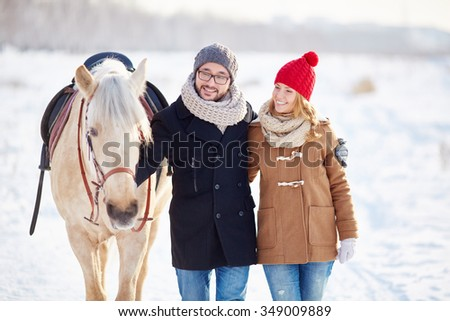 Young couple walking with horse in winter day - stock photo