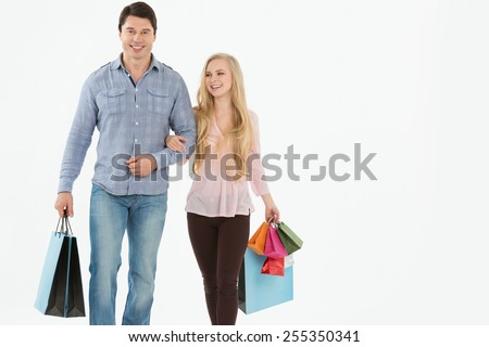 Young couple walking with shopping bags on a white background