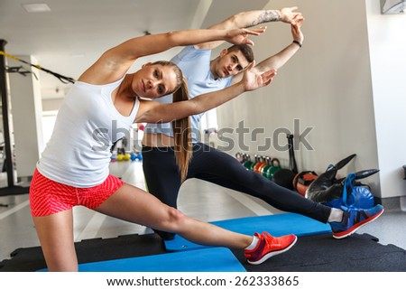 Young couple warming up and doing stretches a the gym - stock photo