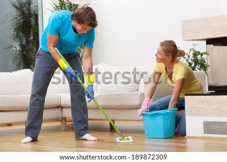Young couple washing the floor together and enjoying that - stock photo
