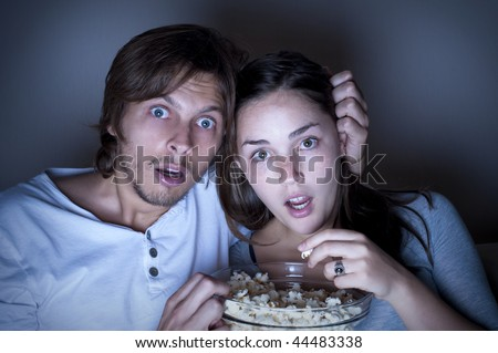 Young couple watch a movie and eat popcorn at home - stock photo