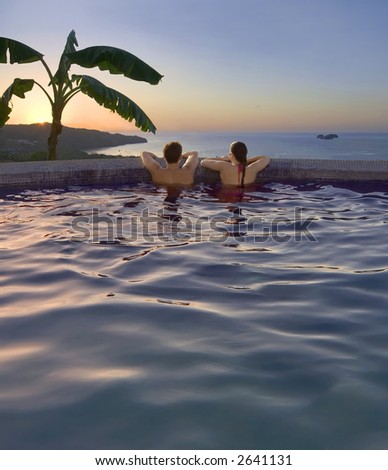 Young couple watches the sunset from an oceanside pool in Costa Rica - stock photo