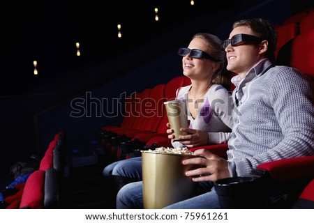 Young couple watching a movie in 3D glasses in cinema - stock photo