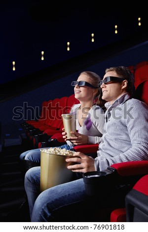 Young couple watching a movie in the cinema - stock photo