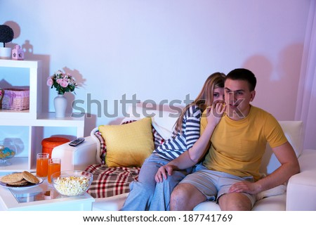 Young couple watching television at home of blacking-out - stock photo