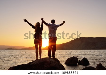Young couple watching the sun, raising his hands to the sky - stock photo