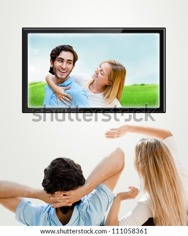 Young couple watching their photos on wide screen tv at home - stock photo