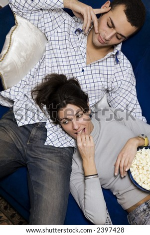 young couple watching tv at home and smiling