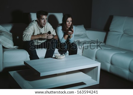 Young couple watching TV late at night - stock photo